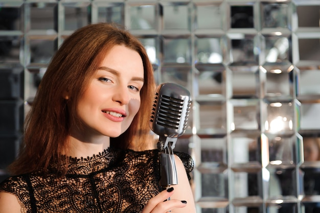 Gwiazda rocka. seksowna dziewczyna śpiewa w mikrofonie retro.