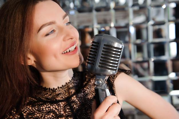 Gwiazda rocka, sexy dziewczyna śpiewa w mikrofon retro