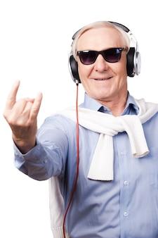 Gwiazda rocka. wesoły starszy mężczyzna w słuchawkach słucha muzyki i pokazuje znak dłoni stojąc na białym tle