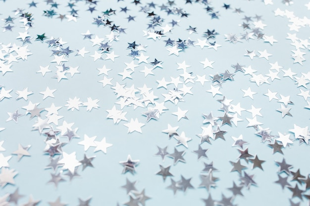 Gwiazdki konfetti srebrnej folii na niebieskim tle