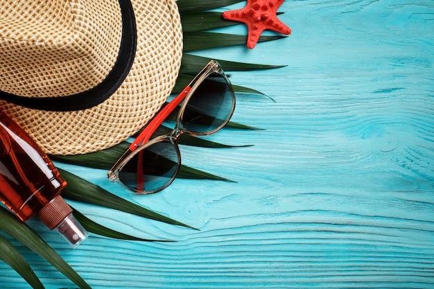 Gwiazdy morskie, kamienie morskie, liście palmowe i muszle leżące na niebieskim tle drewnianych. jest miejsce na etykiety.
