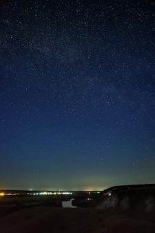 Gwiazdy na nocnym niebie nad doliną rzeki i miastem. kosmiczna przestrzeń