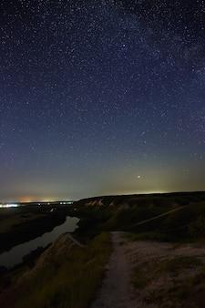 Gwiazdy na nocnym niebie nad doliną rzeki i miastem