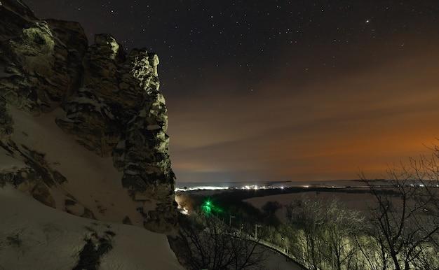 Gwiazdy na nocnym niebie z chmurami. cerkiew prawosławna w górach kredowych. muzeum, rezerwat przyrody, divnogorie. rosja centralna. śnieżny zimowy krajobraz o zmierzchu.