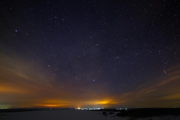 Gwiazdy na nocnym niebie z chmurami. śnieżny zimowy krajobraz o zmierzchu. miasto jest na horyzoncie.