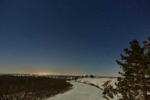 Gwiazdy na nocnym niebie. zimowy pejzaż z zamarzniętą rzeką sfotografowany przy pełni księżyca.