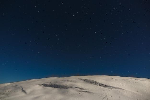 Gwiazdy z chmurami na nocnym niebie nad ośnieżonym grzbietem górskim. tło kosmosu jest fotografowane przy pełni księżyca.