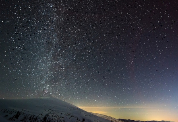 Gwiaździste magiczne niebo z różową mgiełką znajduje się nad zimowym ośrodkiem narciarskim. pojęcie wakacji na wsi i rozkoszowania się nieskazitelną naturą.