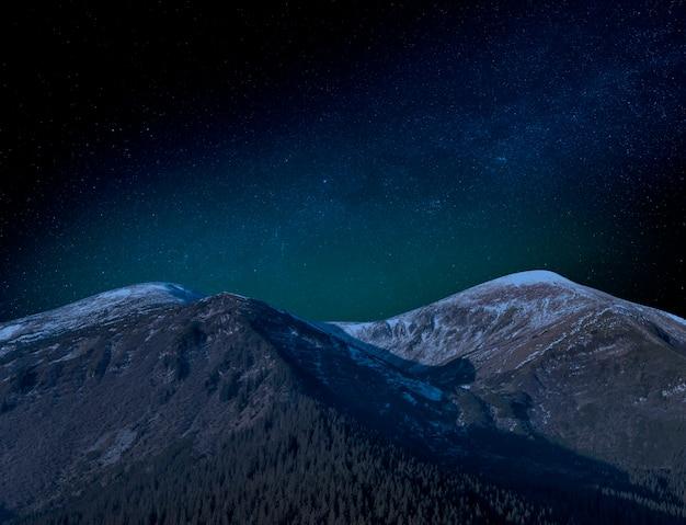 Gwiaździste niebo nad szczytami częściowo pokrytych śniegiem gór. malowniczy nocny krajobraz.