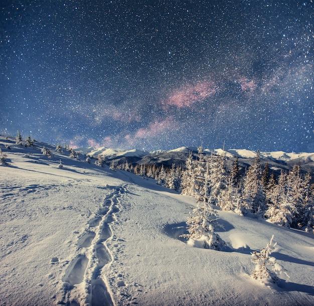 Gwiaździste niebo w zimową śnieżną noc. fantastyczna droga mleczna