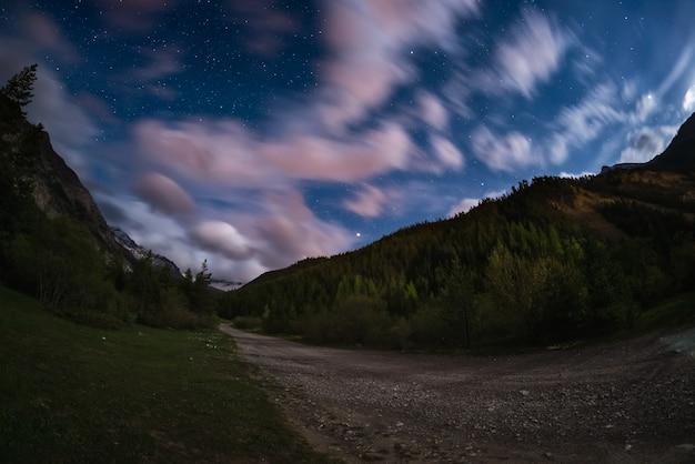 Gwiaździste niebo z kolorowymi chmurami i jasnym blaskiem księżyca