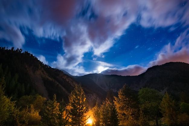 Gwiaździste niebo z niewyraźnymi chmurami ruchu i jasnym blaskiem księżyca, uchwycone z lasu modrzewiowego, świecące przez płonący ogień. rozległy nocny krajobraz w europejskich alpach. przygoda w dziczy.
