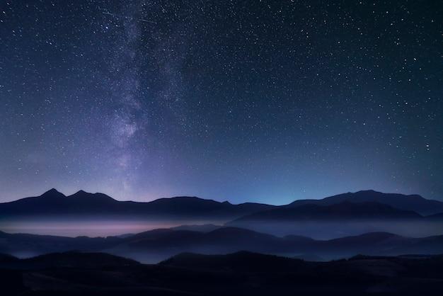 Gwiaździste nocne niebo z drogą mleczną nad górami.