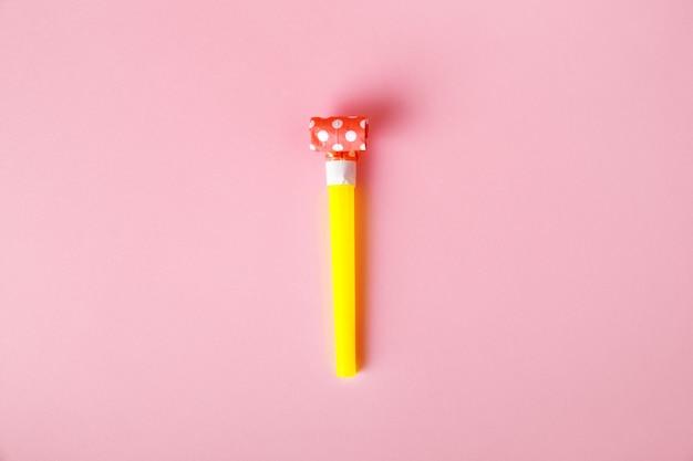Gwizdek imprezowy lub dmuchawa na różowym tle, akcesoria do imprez i uroczystości