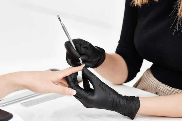 Gwoździarz robi manicure'owi w salonie. korzystanie z narzędzi do manicure.