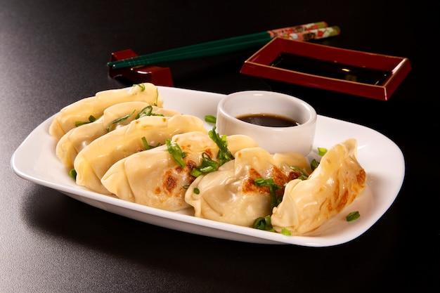 Gyoza lub makaron z nadzieniem z wołowiny, wołowiny lub wieprzowiny lub warzyw. dania kuchni azjatyckiej