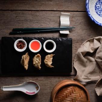 Gyoza, pierogi parzone i grillowane, podawane z sosem 3 rodzajów na czarnym kamiennym talerzu