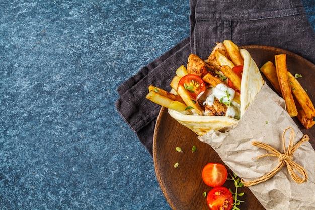 Gyros souvlaki zawija się w chleb pita z kurczakiem, ziemniakami i sosem tzatziki.
