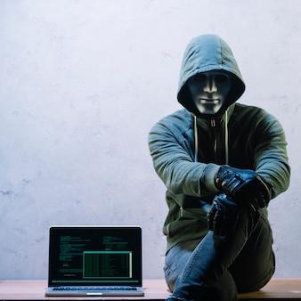 Hacker siedzi obok laptopa