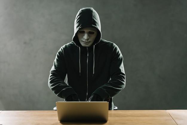Hacker z laptopem na stole