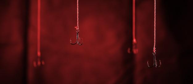 Haczyki wędkarskie wiszą na ciemnym tle. pojedynczy hak w zbliżeniu ostrości.