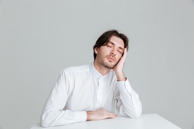 Hadsome młody mężczyzna w białej koszuli śpiący siedząc przy biurku odizolowany na szarej ścianie