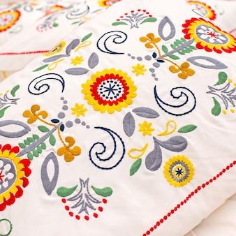 Haftowany wzór poduszki znajduje się na łóżku.
