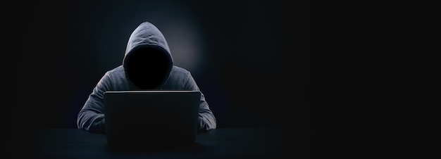 Haker bez twarzy w kapturze w ciemności