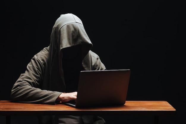 Haker bez twarzy w kapturze z laptopem na czarnym tle