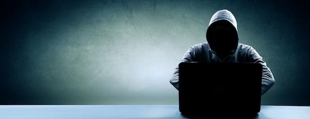 Haker drukuje kod na klawiaturze laptopa, aby włamać się do cyberprzestrzeni