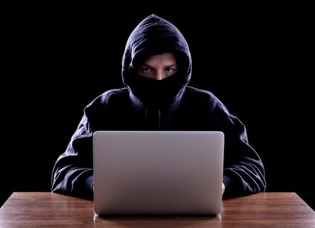 Haker komputerowy kradnie dane z laptopa
