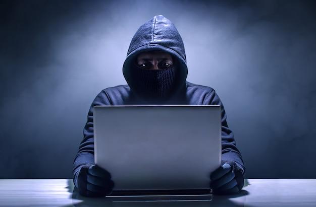 Haker korzysta z laptopa. włamywanie się do internetu.