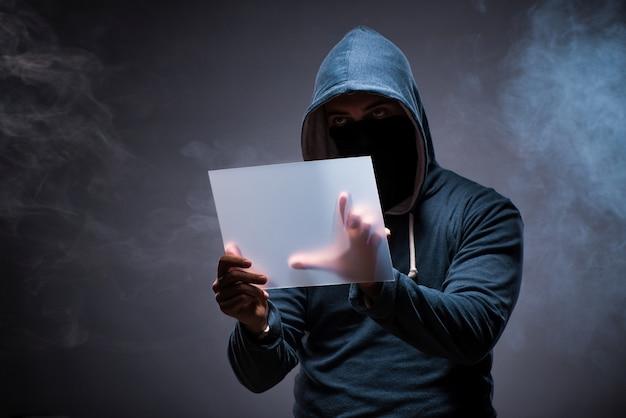 Haker pracuje na tablecie w ciemności