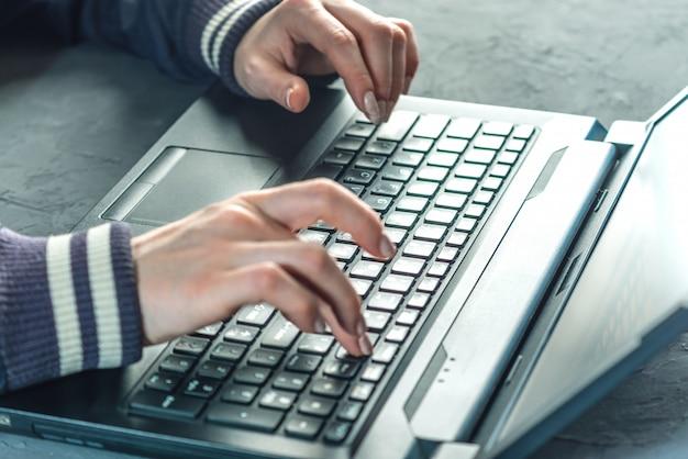 Haker programista pisze na klawiaturze laptopa, aby zhakować system.