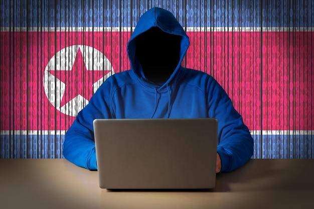 Haker siedzi przed laptopem na tle cyfrowej flagi korei północnej