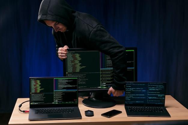 Haker trzymający monitor ze średnim strzałem