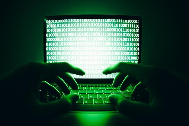 Haker używający laptopa do kodowania wirusa lub złośliwego oprogramowania do włamywania się do serwera internetowego cyberatak
