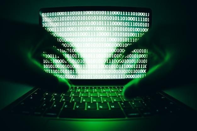 Haker używający laptopa do kodowania wirusa lub złośliwego oprogramowania w celu włamania się do serwera internetowego