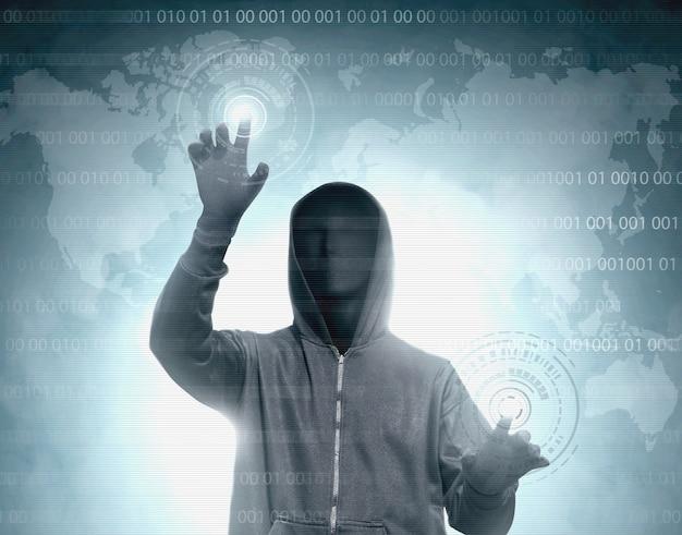 Haker w czarnej bluzie z kapturem dotykający wirtualnego ekranu z kodem binarnym
