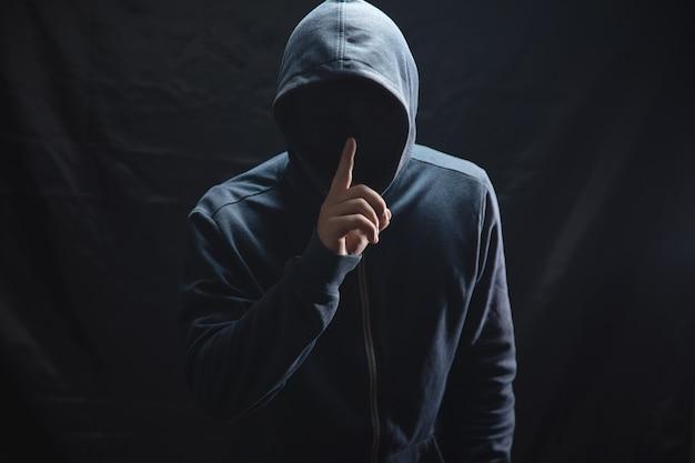 Haker w kapturze robi gest ciszy