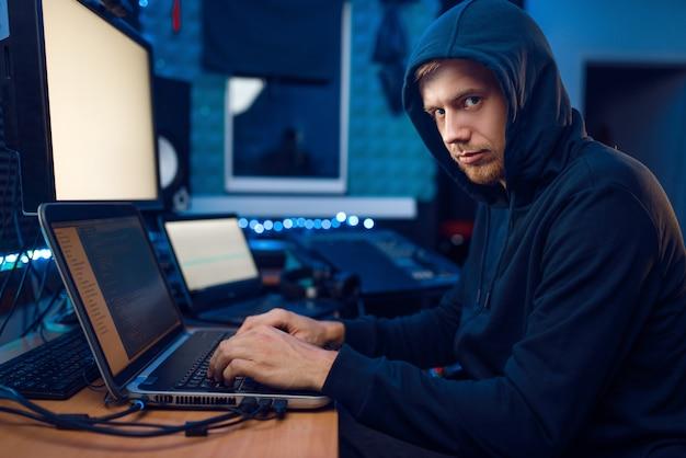 Haker w kapturze siedzący przy laptopie, hakowanie informacji. szpieg internetowy, męski programista próbujący włamać się do zaszyfrowanej sieci
