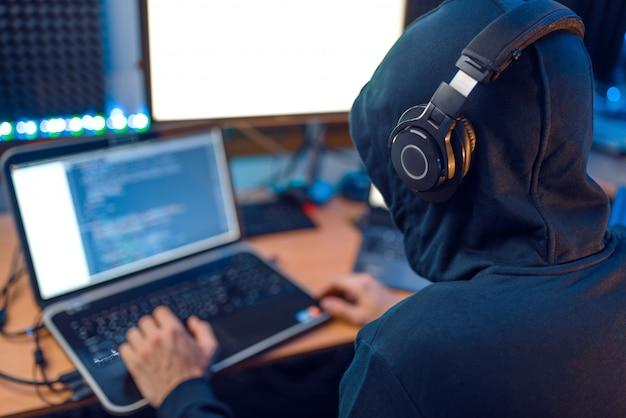 Haker w kapturze siedzi przy laptopie, widok z tyłu
