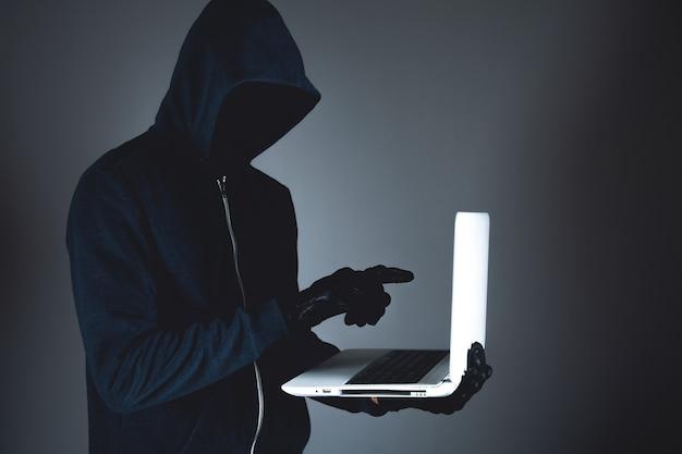 Haker z laptopem. przestępstwo komputerowe.