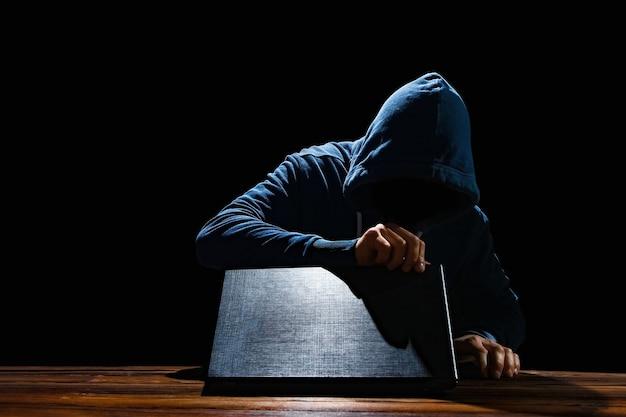 Haker z laptopem przy stole włamuje się do systemu