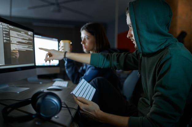 Hakerzy płci męskiej i żeńskiej pracują na komputerach w darknecie, niebezpiecznej pracy zespołowej. nielegalny programista internetowy w miejscu pracy, zawód przestępczy. hackowanie danych, cyberbezpieczeństwo