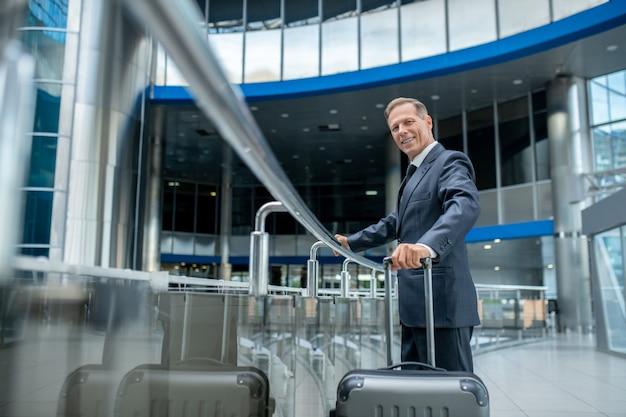 Hala odlotów. uśmiechnięty dobrze wyglądający biznesowy dorosły mężczyzna w garniturze z walizką w poczekalni na lotnisku