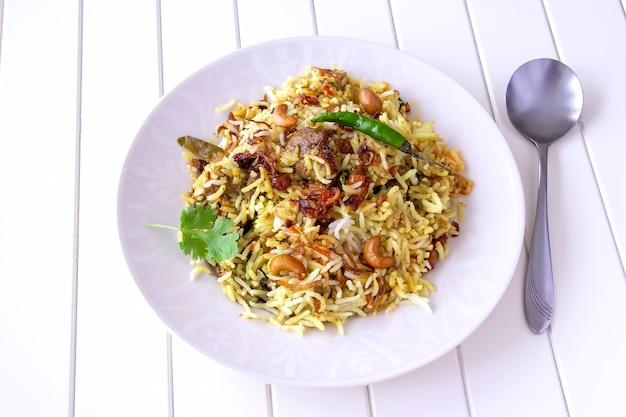 Halal indyjski kurczak biryani na talerzu z łyżką. białe tło. selektywne skupienie. widok z góry.