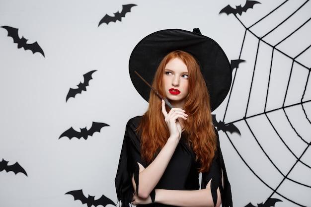 Halloween concept - piękna czarownica bawi się magicznym kijem na szarej ścianie.