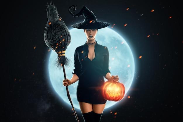 Halloween czarownica dziewczyna z miotłą w dłoniach na tle księżyca. piękna młoda kobieta w kapeluszu czarownicy wyczarowuje. imprezy halloween, przestrzeń do kopiowania, media mieszane.