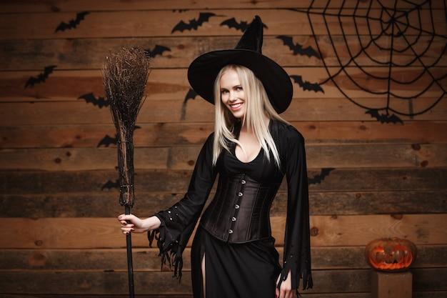 Halloween czarownica koncepcji - happy halloween sexy witch gospodarstwa stwarzaję ... cych na tle starego drewnianego studio.